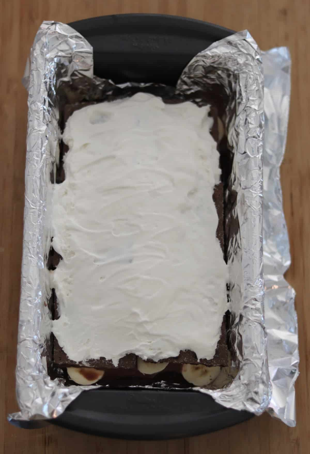 Frozen whipped topping covered chocolate fudge ice box cake in foil-lined loaf pan.