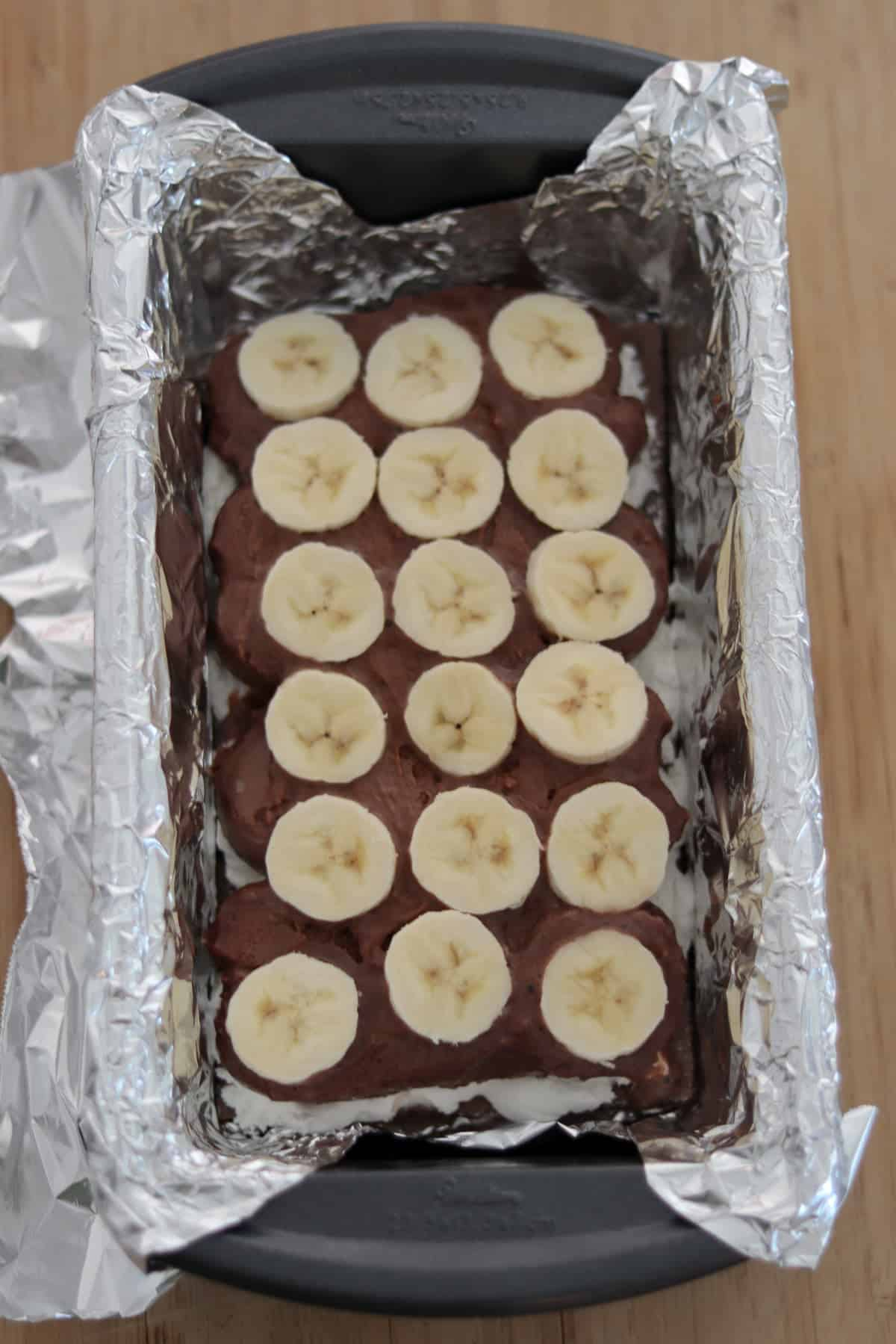 Foil-lined-loaf pan with chocolate ice cream fudge bars topped with banana slices.