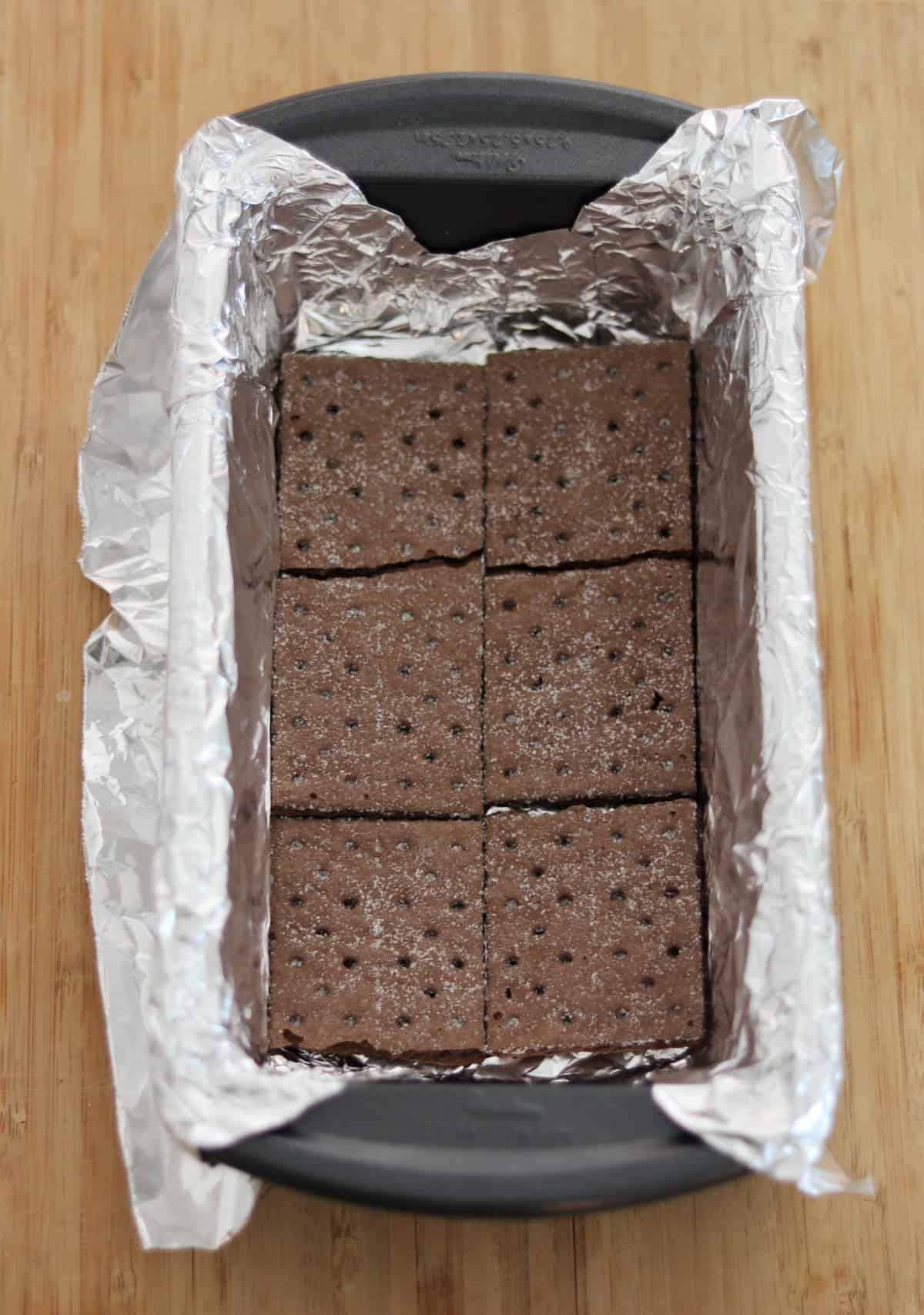 Foil lined loaf pan with layer of chocolate graham crackers.