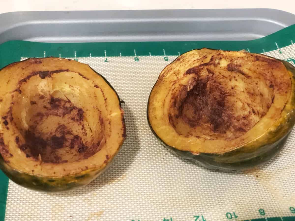 Oven-roasted acorn squash on baking mat lined baking sheet.