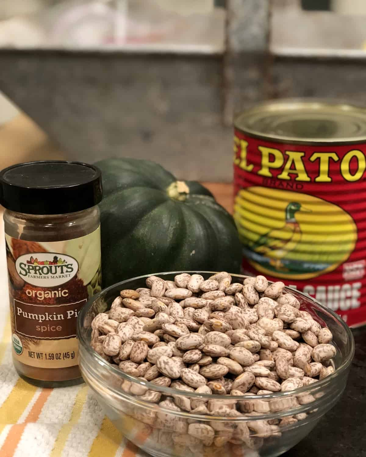 Uncooked pinto beans, pumpkin pie spice, acorn squash and can of enchilada sauce on kitchen counter.