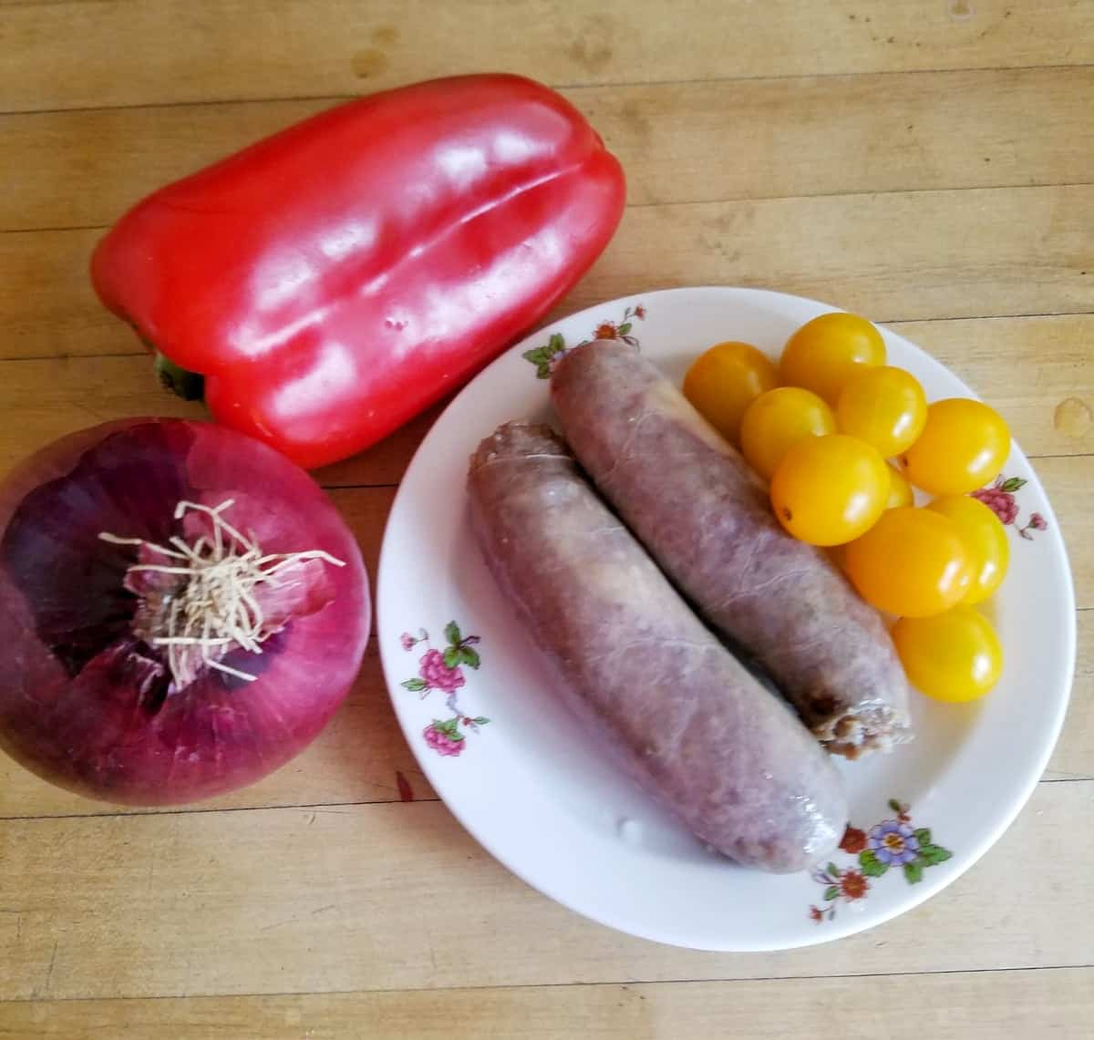 Two sausage links and cherry tomatoes on plate near red onion and red pepper on cutting board.