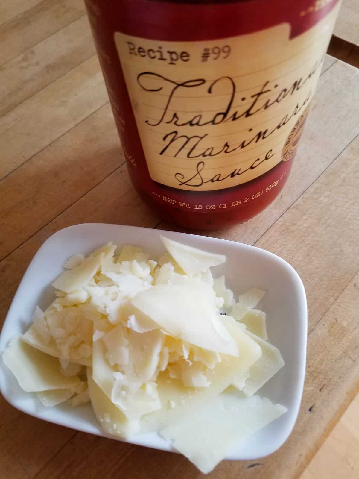 Jar of marinara sauce near shaved parmesan cheese on small white plate.