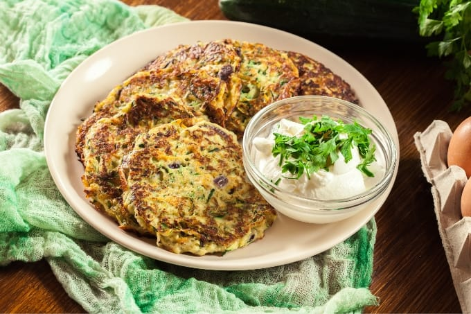 Shredded zucchini pancakes on platter with side dish of sour cream.