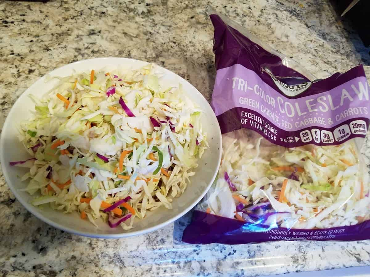 Bag of tri-color coleslaw mix with some in white bowl on granite counter.