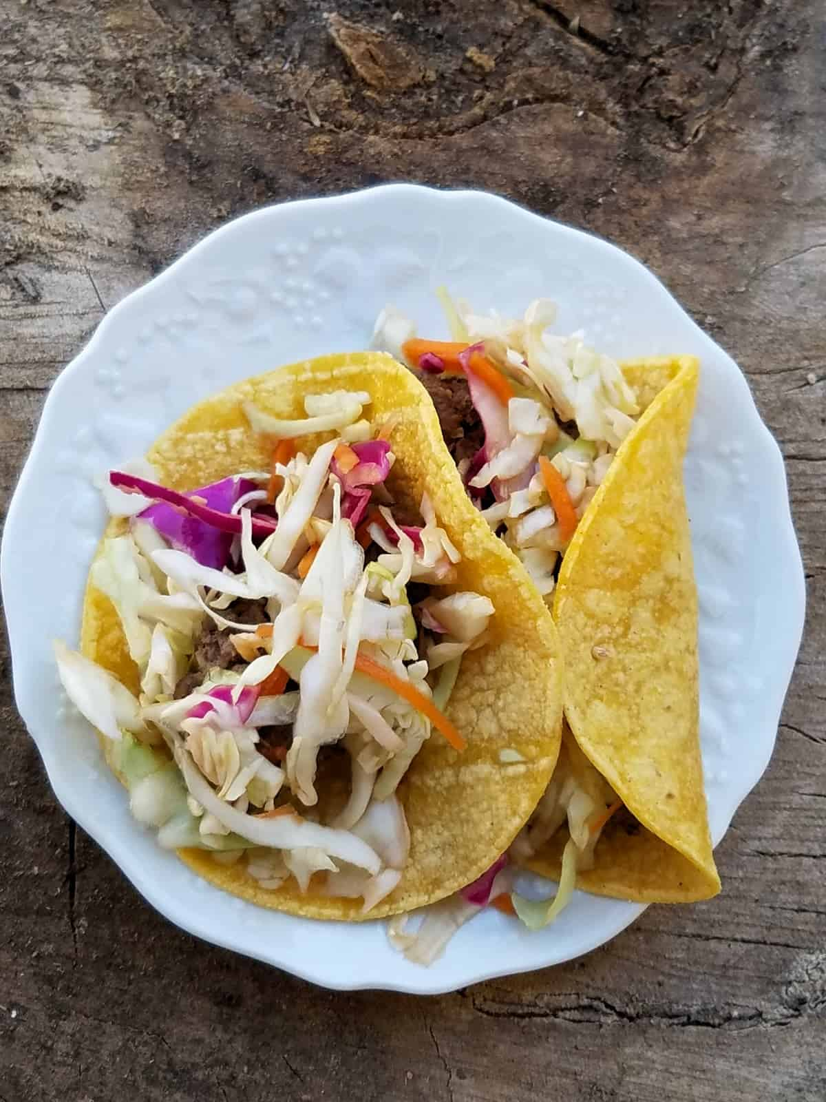 Two Asian style pork tacos in white plate.
