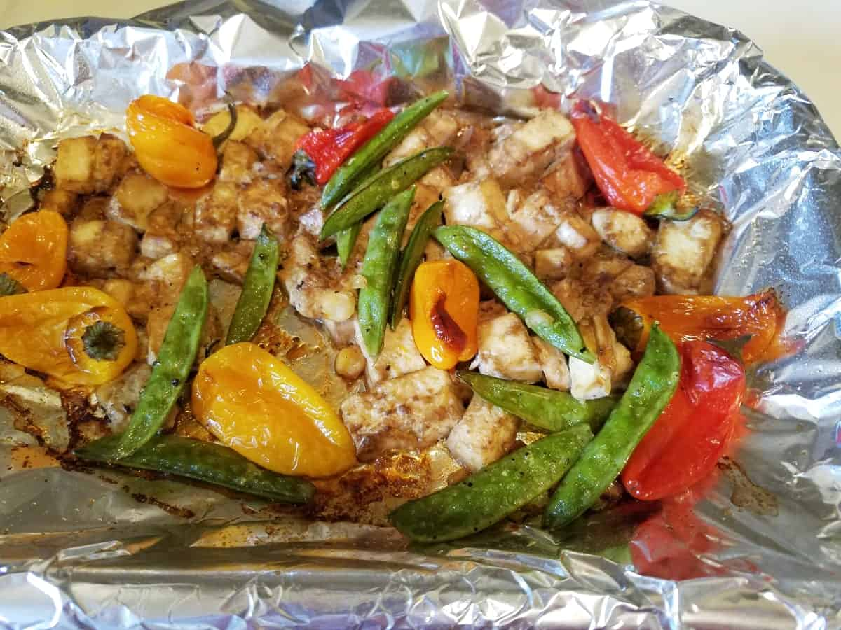 Baked sesame ginger tofu with peppers and snap peas on foil-lined pan