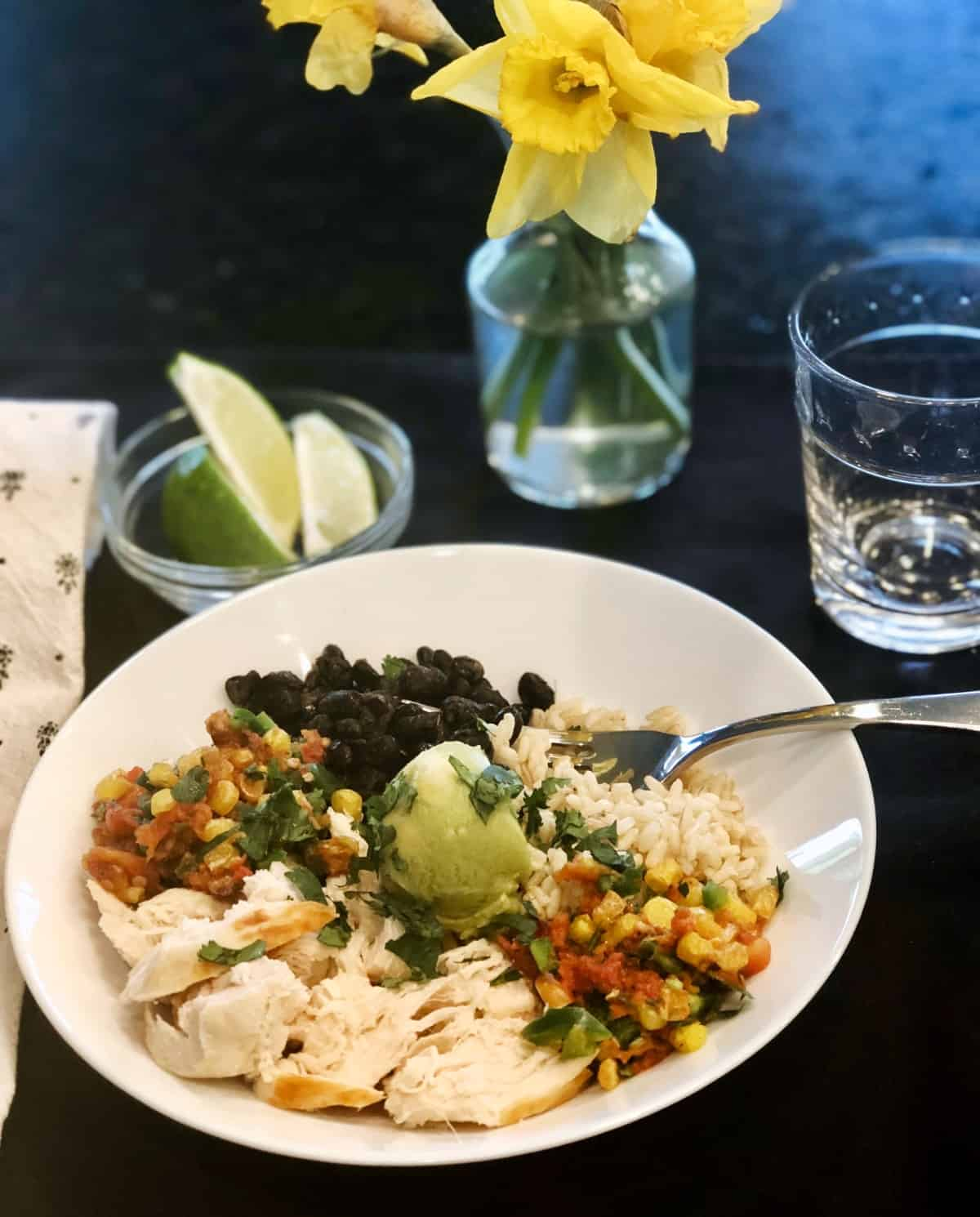 Chicken and black bean bowl on dinner table with lime slices and fresh flowers.