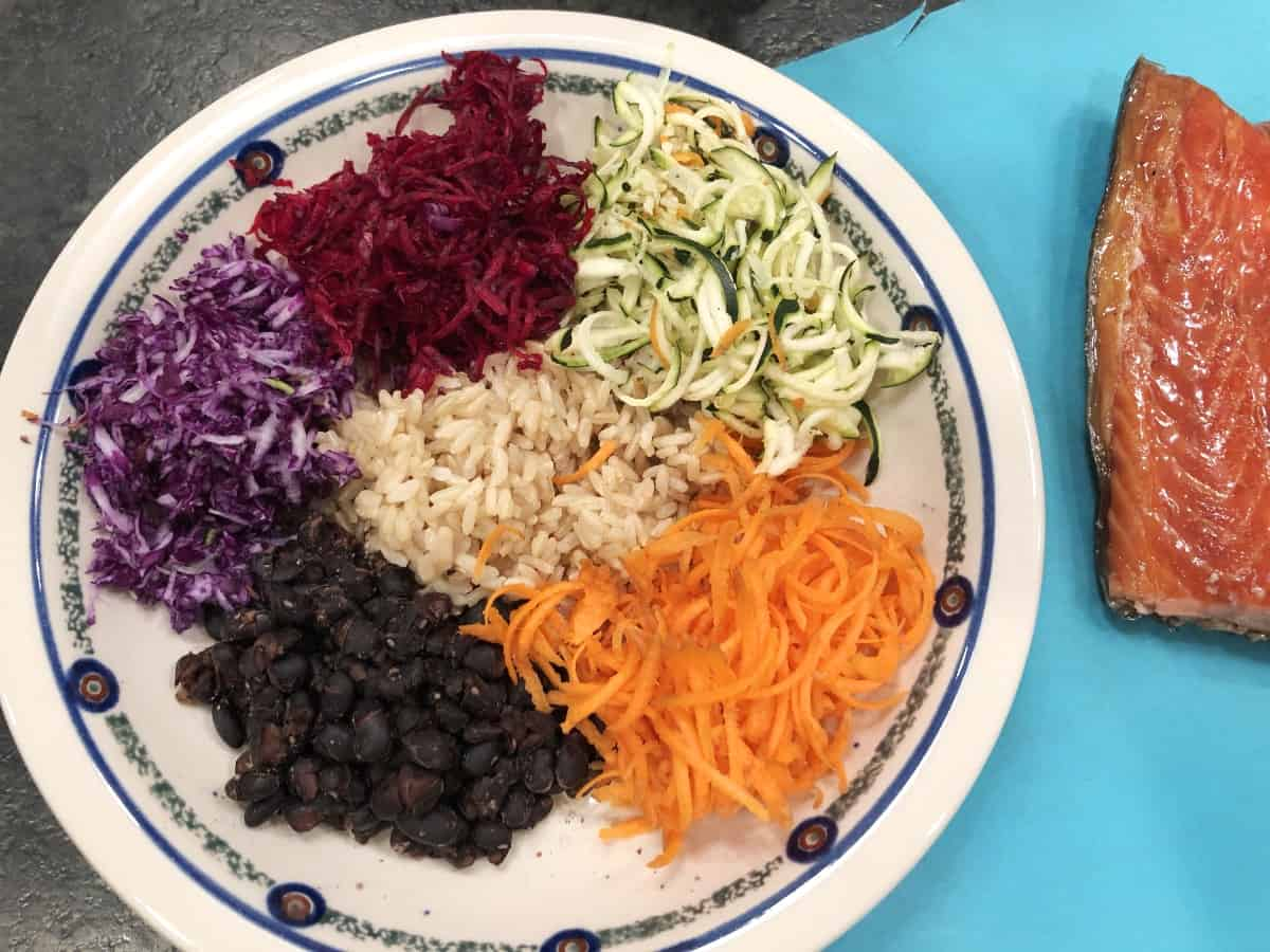 Bowl with brown rice, shredded carrots, zucchini, beets, cabbage, and black beans with chunk of salmon.