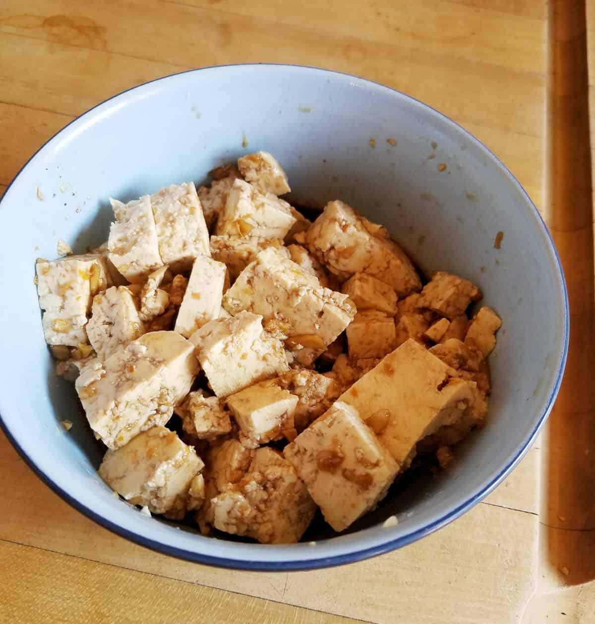 Cubed tofu marinating in sesame ginger soy sauce in small white bowl.