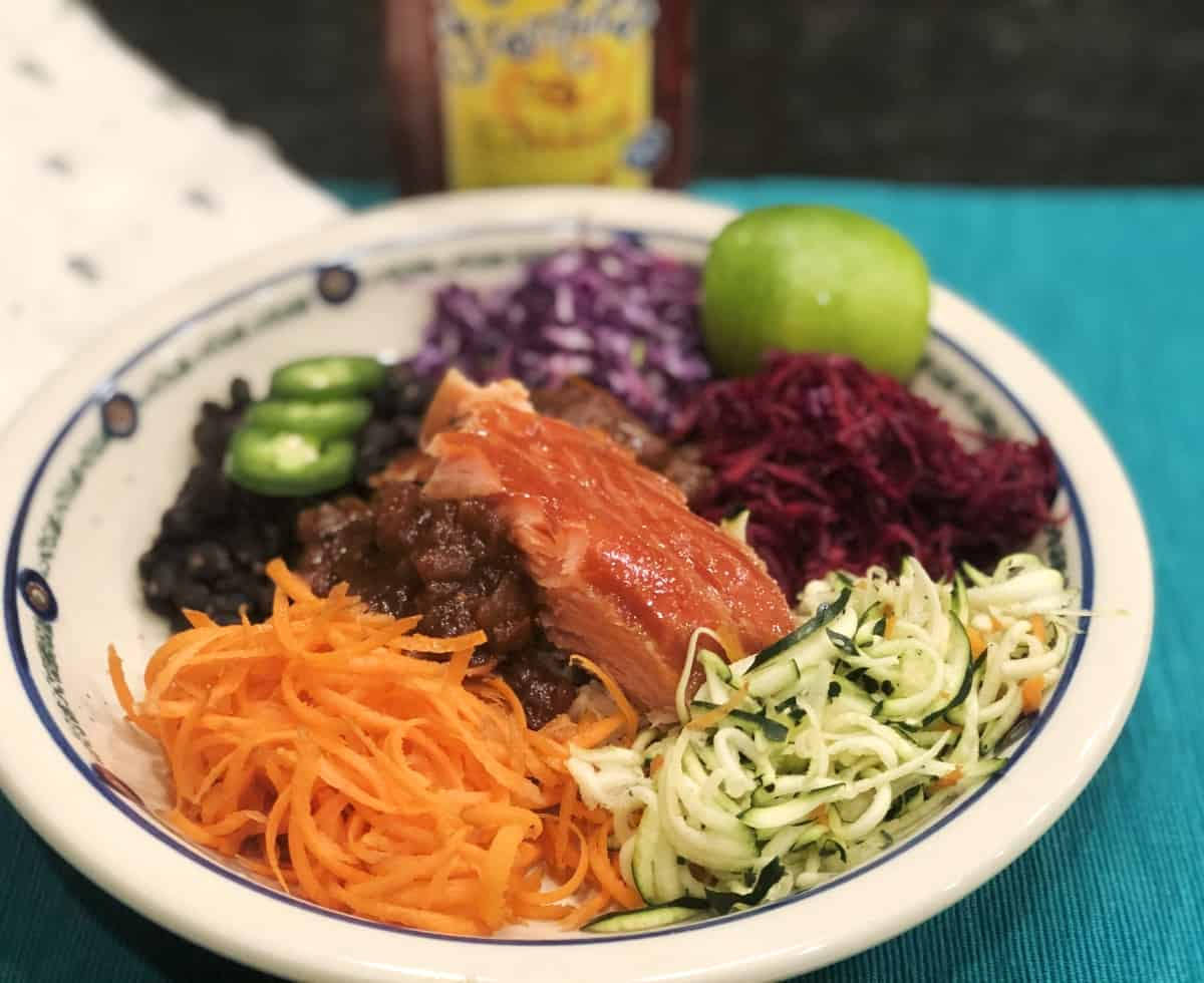 Salmon power bowl with shredded carrots, zucchini, cabbage, black beans and salsa.