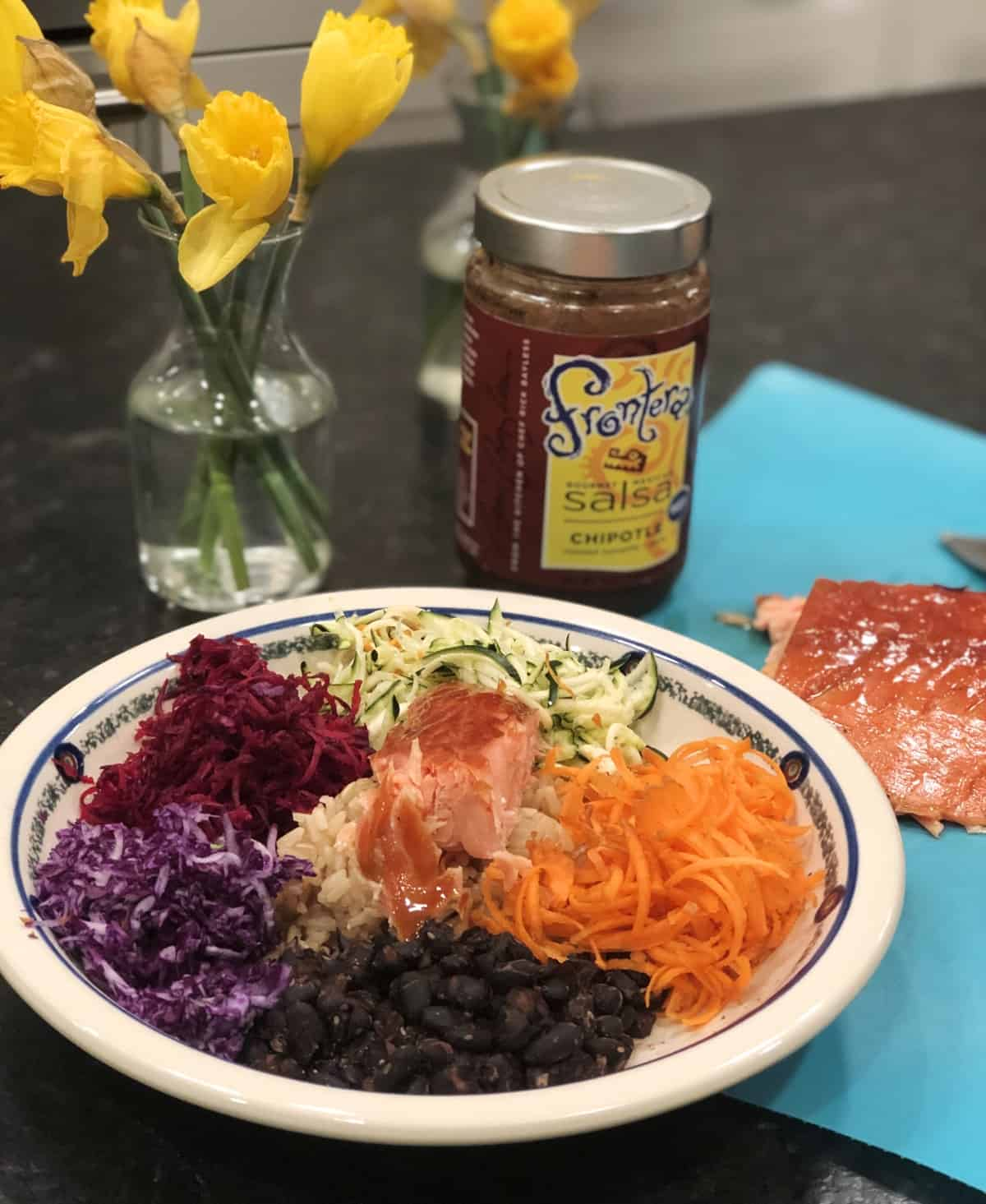 Salmon power bowl with black beans, shredded carrots, zucchini, beets and cabbage and jar of salsa in the background.