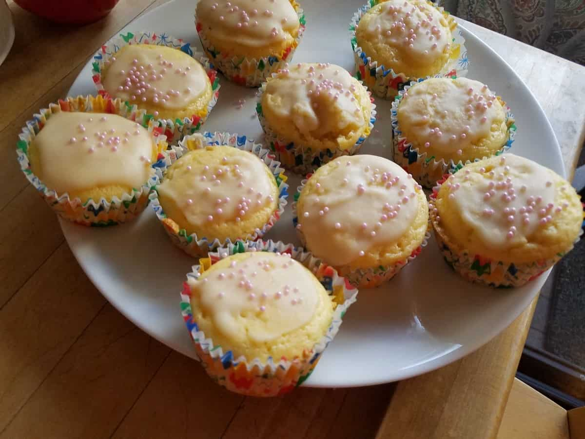 Two ingredient 7-up cake mix cupcakes with icing and sprinkles on white platter.