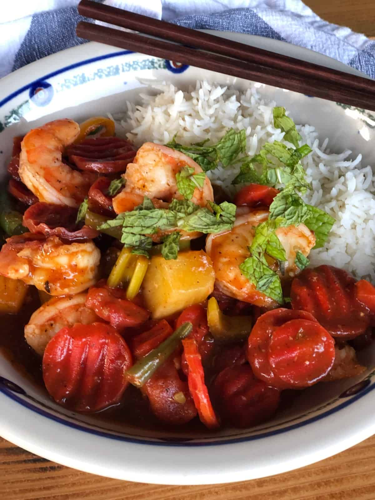 Caribbean shrimp and vegetables with white rice in bowl with chopsticks.