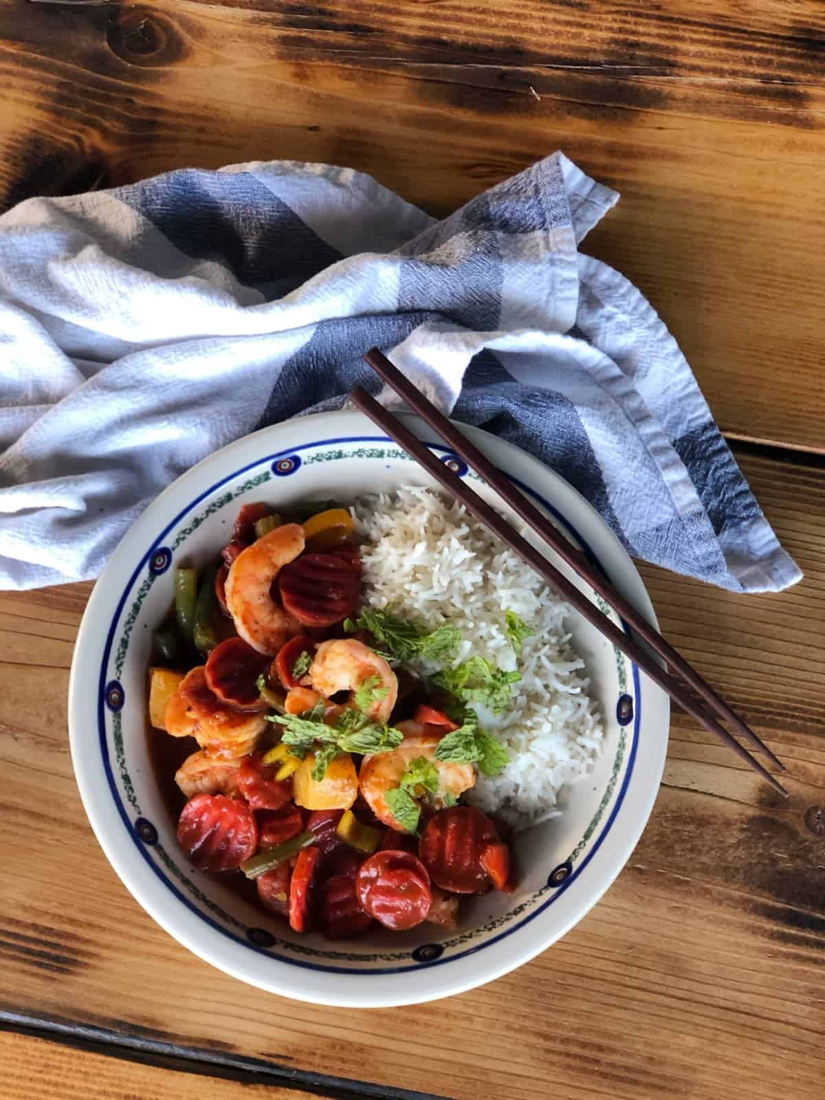 Caribbean shrimp and vegetables with white rice in bowl with chopsticks and blue napkin on wooden table.