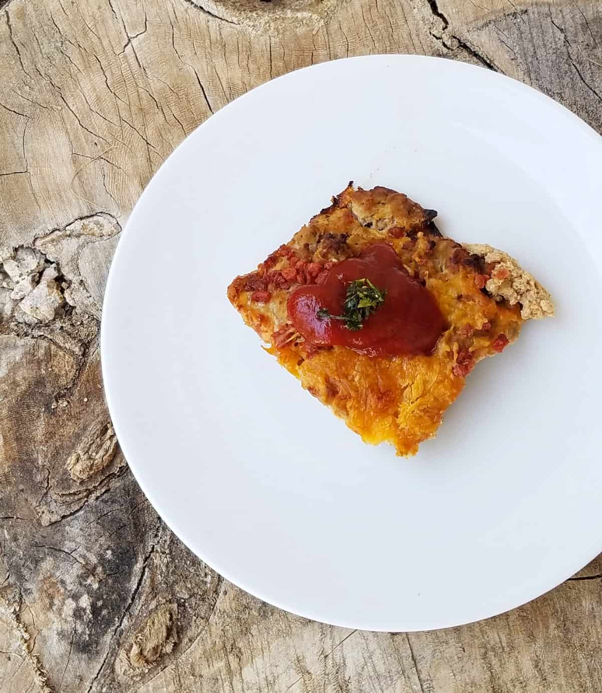 Piece of baked cheeseburger casserole topped with ketchup on white dinner plate.
