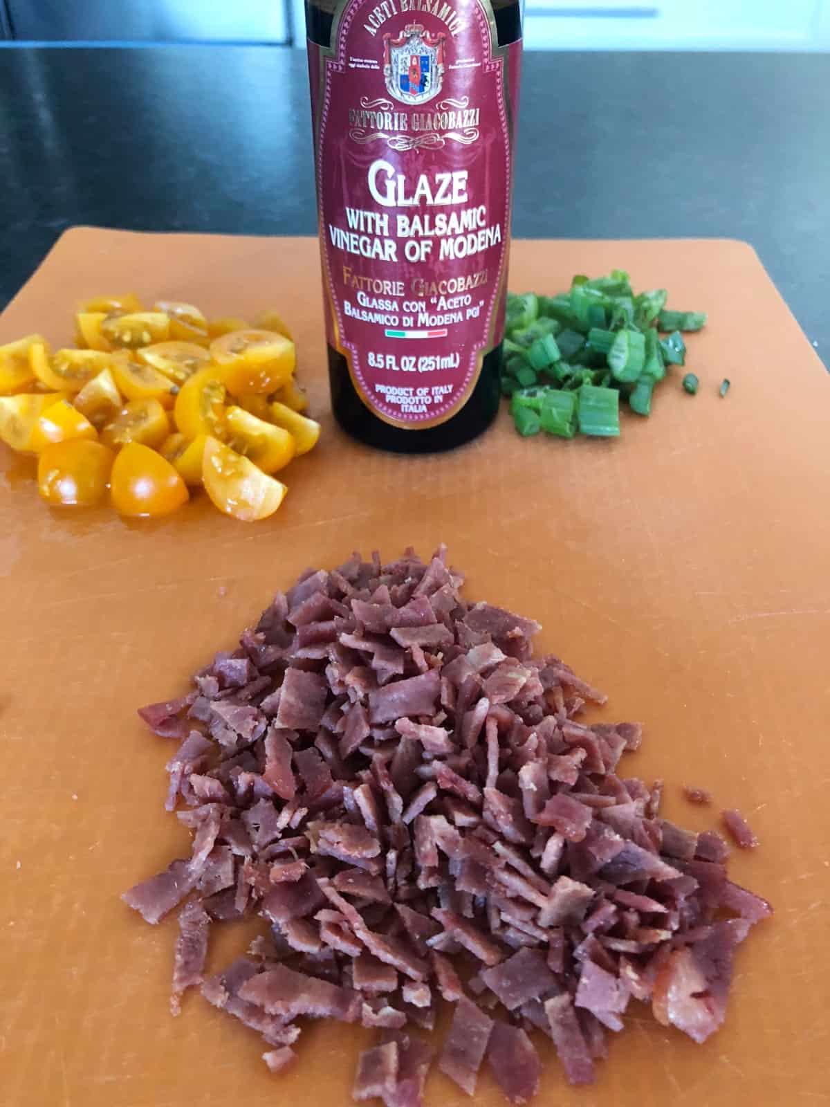 Chopped tomatoes, sliced green onion, chopped turkey bacon, balsamic glaze on orange cutting mat.