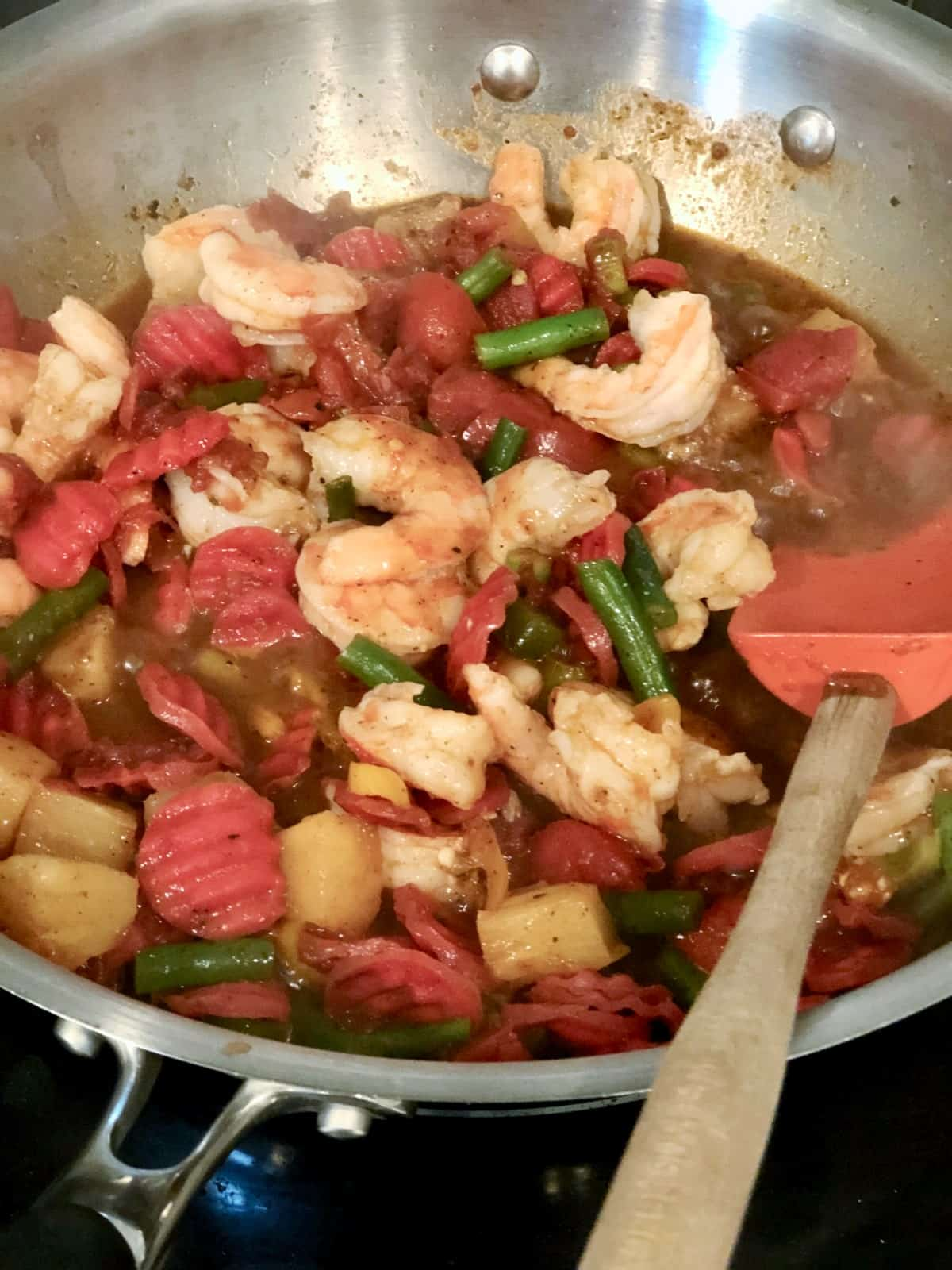 Cooking Caribbean Shrimp and Vegetable Stir Fry in wok with spatula.