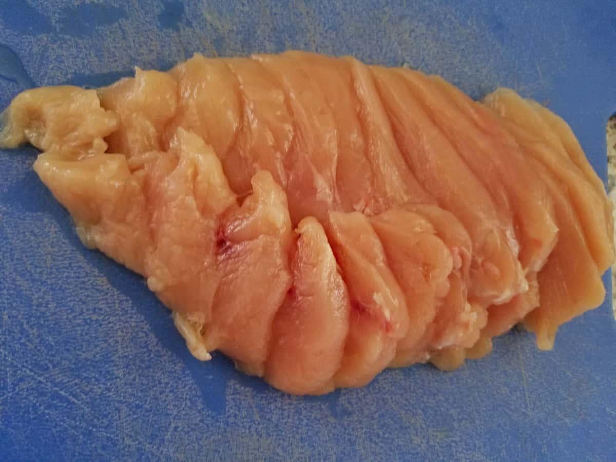 Sliced chicken breast on blue cutting board.