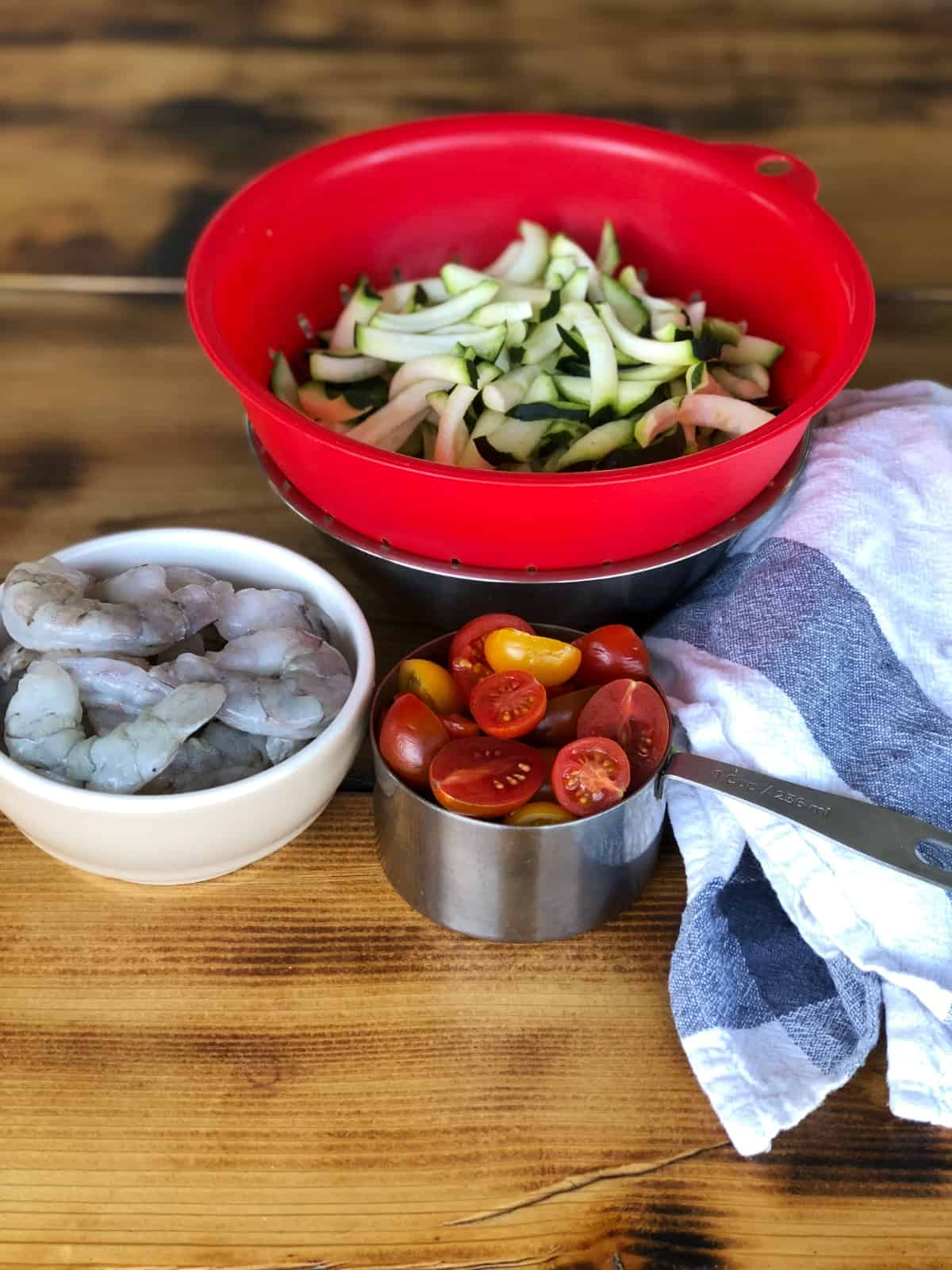 Sliced zucchini in red colander, raw shrimp and chopped tomatoes on wooden table.