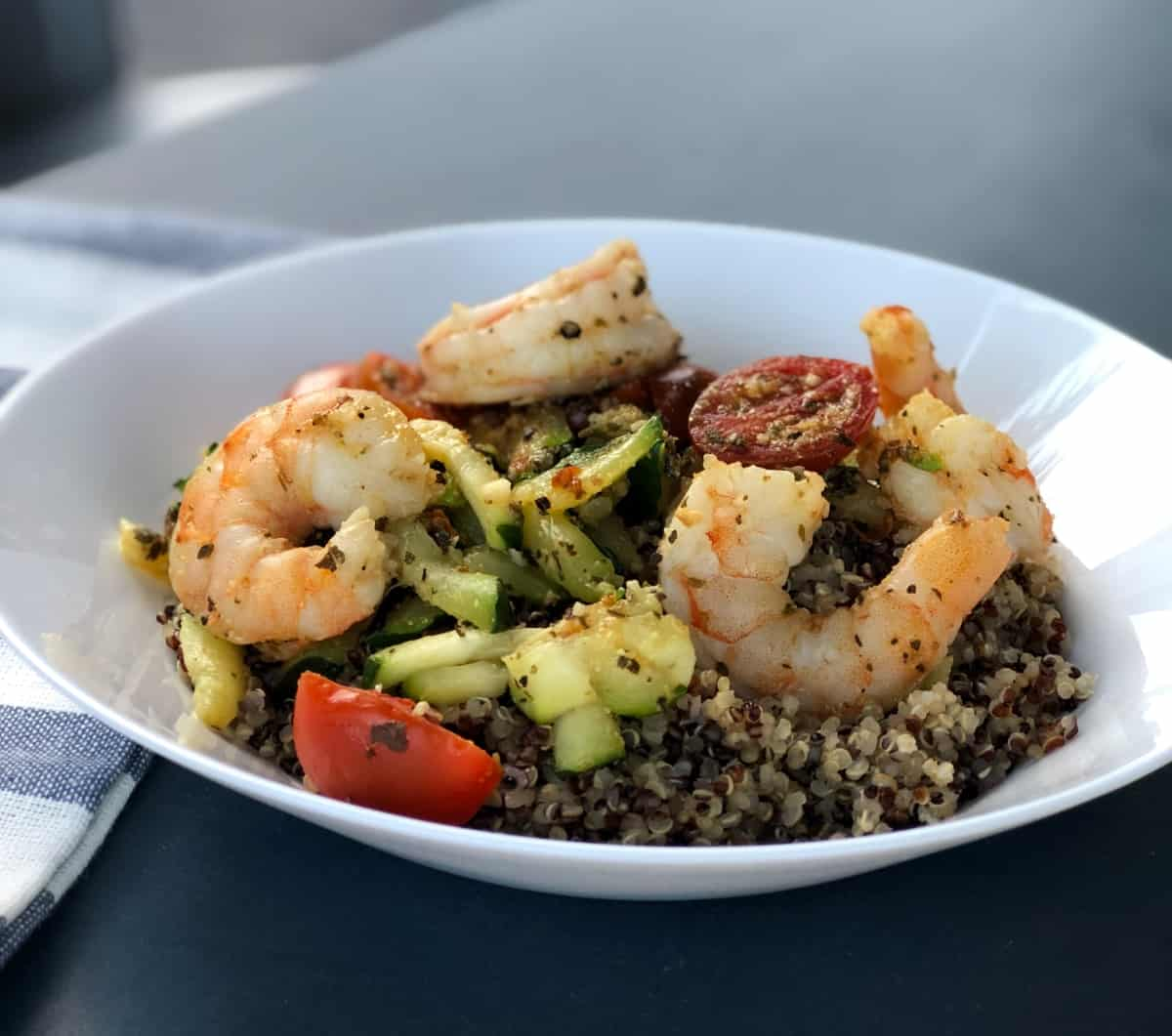 Spicy shrimp with zucchini and tomatoes over quinoa in white bowl.