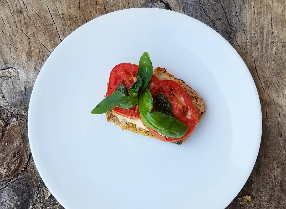 Oven-baked caprese sandwich on white plate.