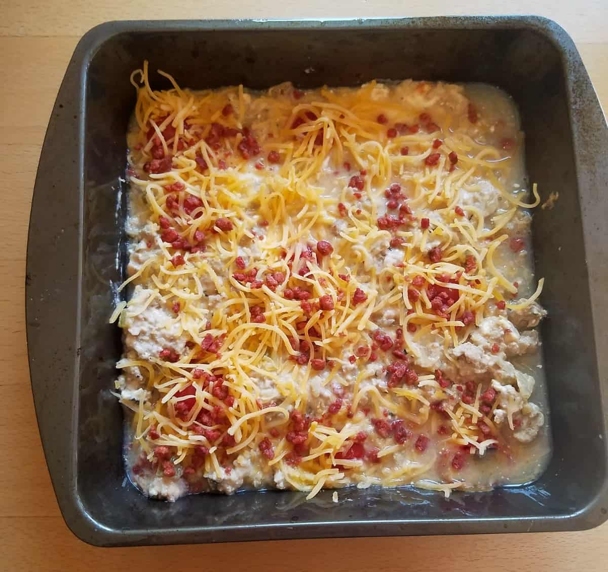 Unbaked cheeseburger casserole topped with shredded cheese and bacon bits in baking dish.