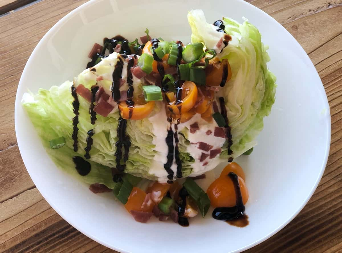 Iceberg wedge topped with tomatoes, green onion, bacon bits, creamy blue cheese and balsamic glaze.