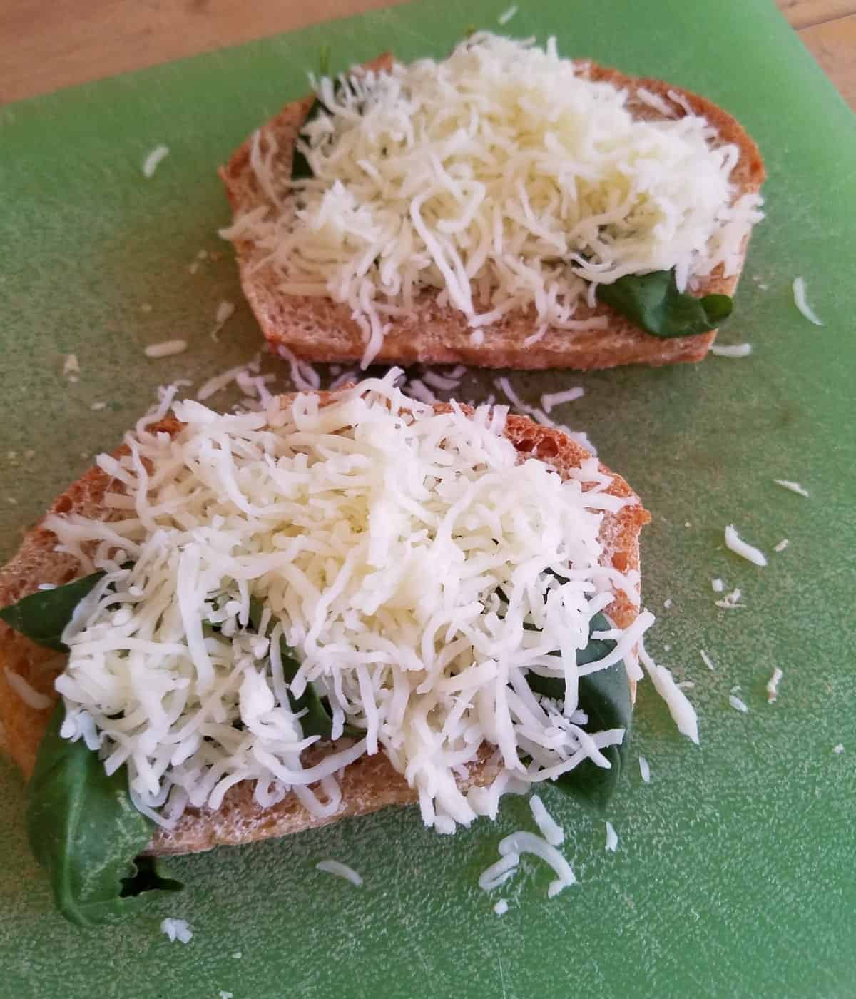 Wheat bread topped with fresh basil leaves and shredded mozzarella.