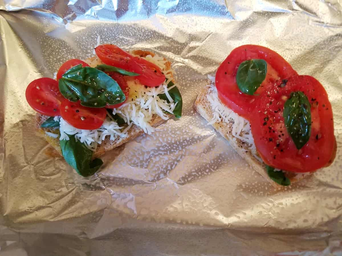 Wheat bread topped with fresh basil, sliced tomatoes and shredded mozzarella on foil-lined baking sheet.