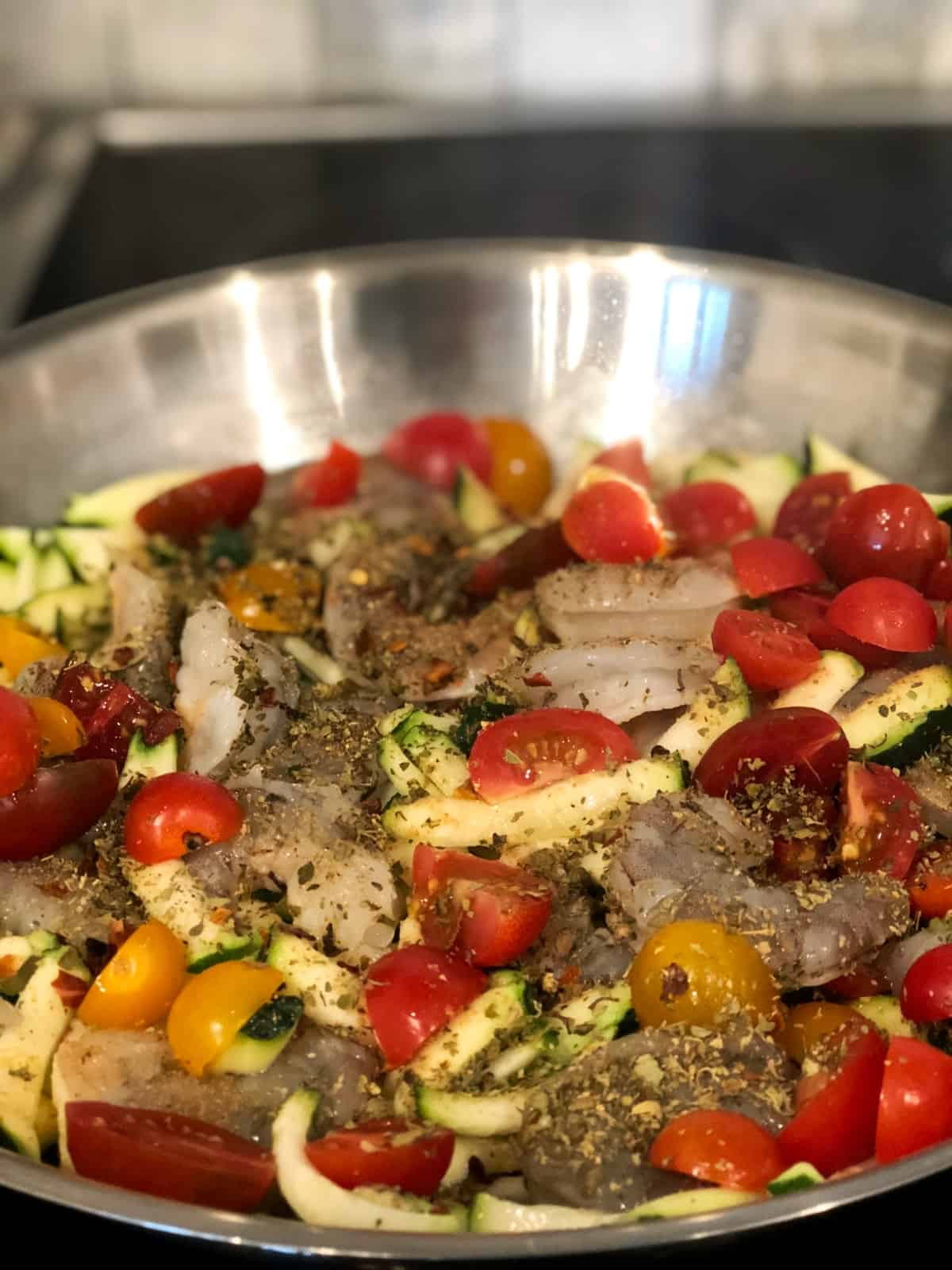 Uncooked shrimp, zucchini, tomatoes and spices in saute pan.