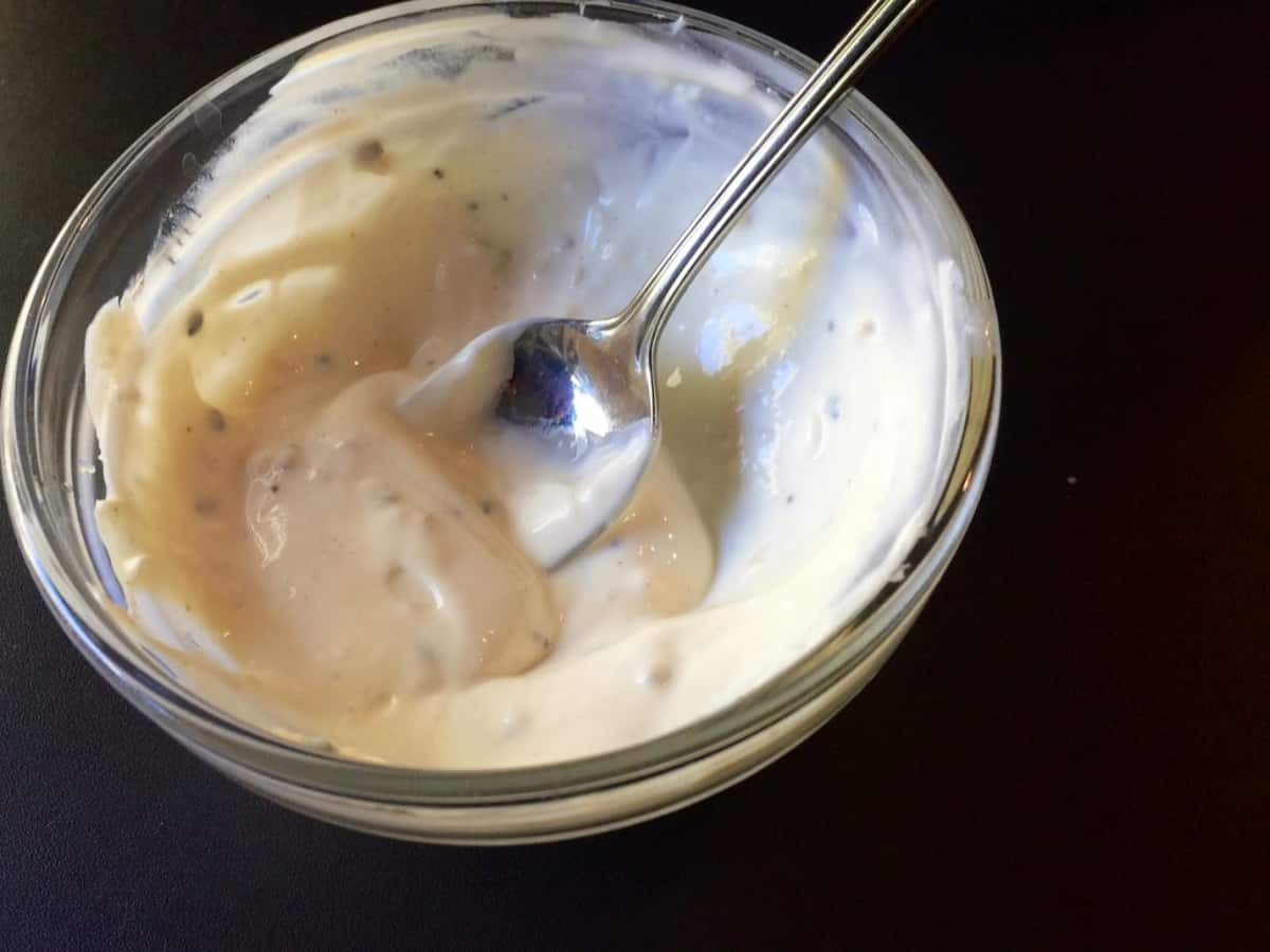 Creamy everything bagel salad dressing in glass bowl with spoon.