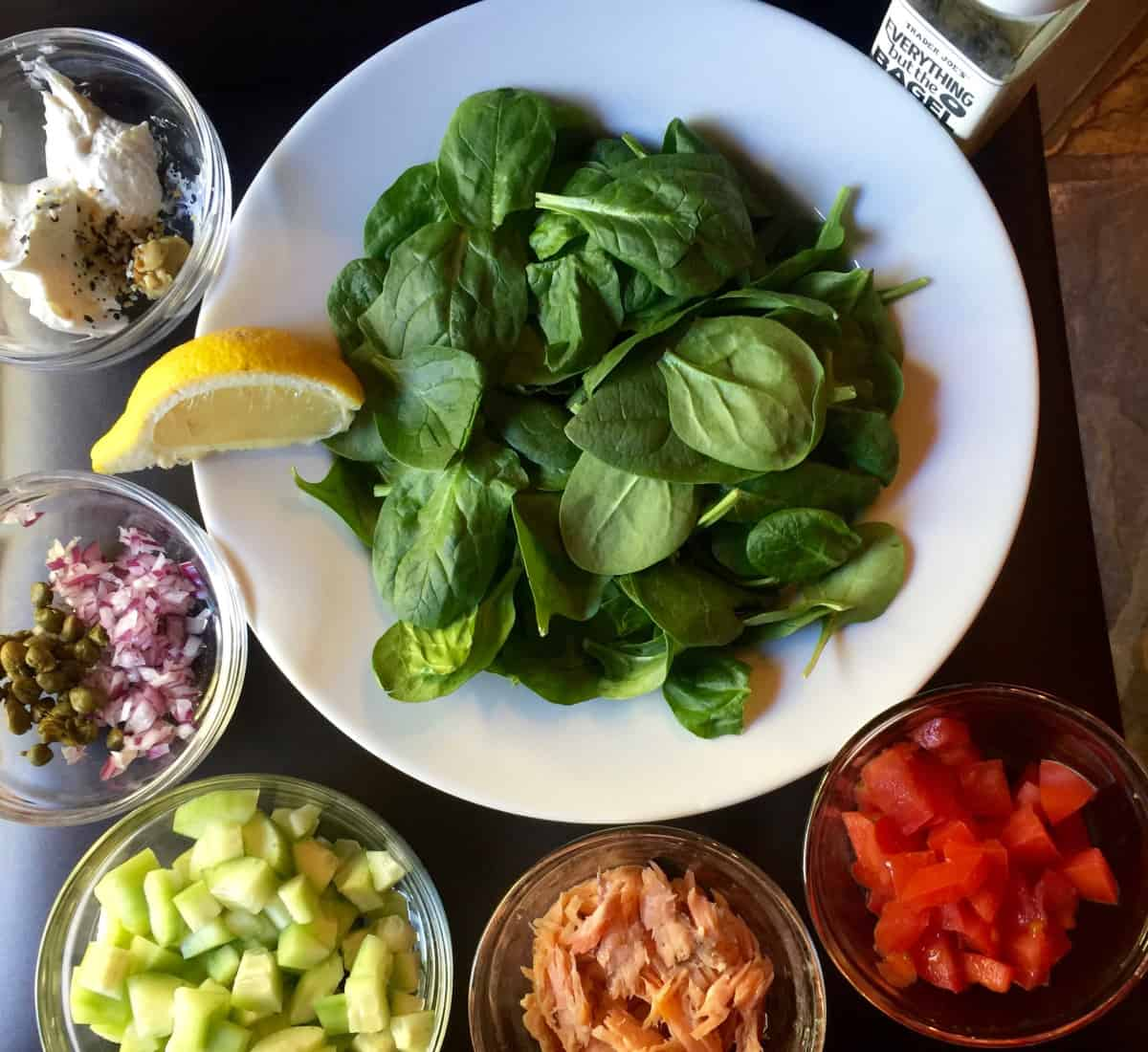 Baby spinach, cucumber, smoked salmon, tomato, red onion and capers for making salad.