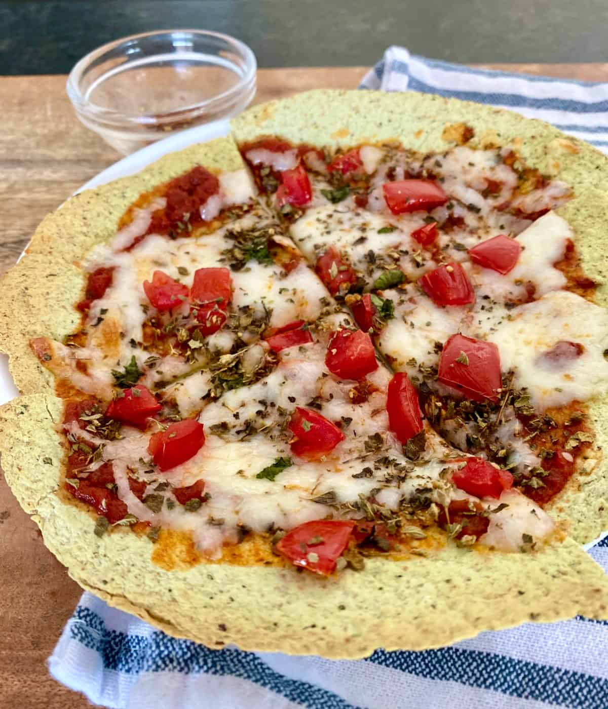 Baked tortilla pizza topped with cheese, tomatoes and basil with crushed red pepper flakes in background.