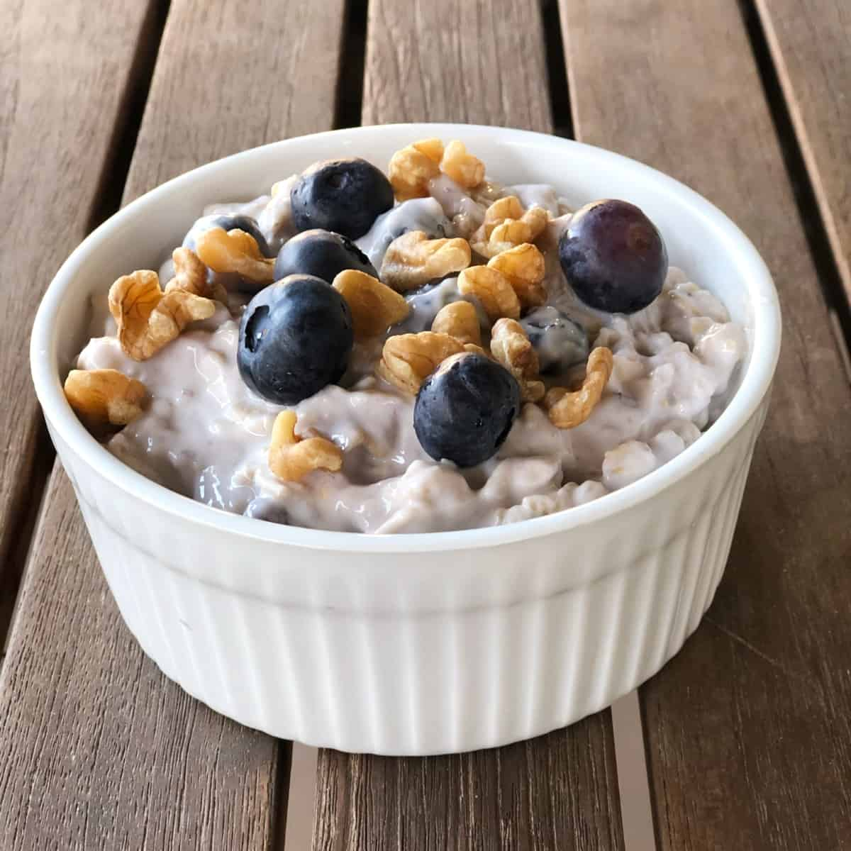 Blueberry maple overnight oats topped with toasted walnuts and fresh blueberries in small white ramekin