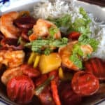 Caribbean shrimp and vegetables stir-fry with white rice in bowl with chopsticks.