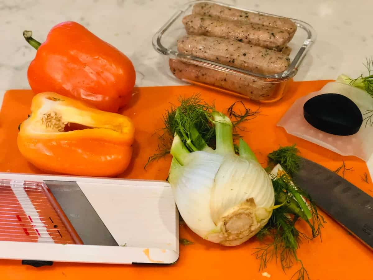 Chicken sausages, yellow and orange bell peppers and fennel bulb on orange cutting mat with mandolin and chef's knife.