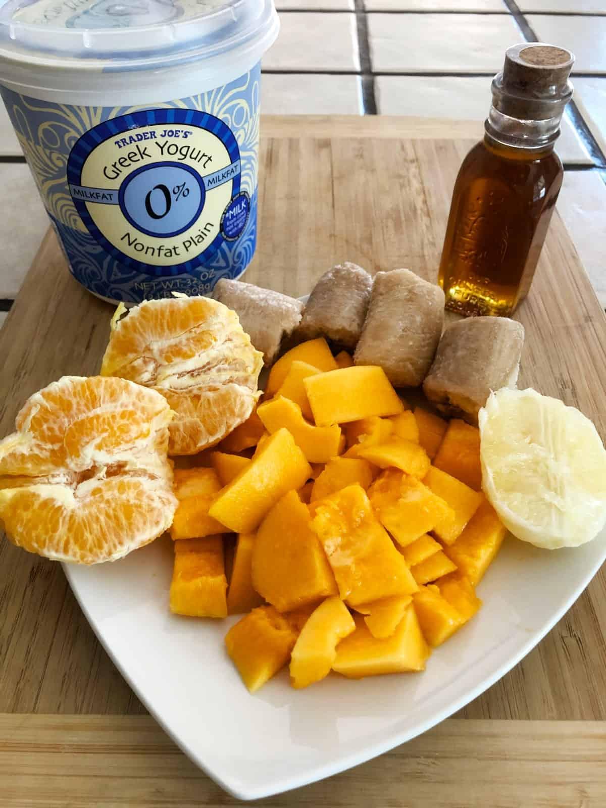 Halved peeled orange, chopped papaya, half peeled lemon, frozen banana chunks, honey and Greek yogurt on bamboo cutting board.