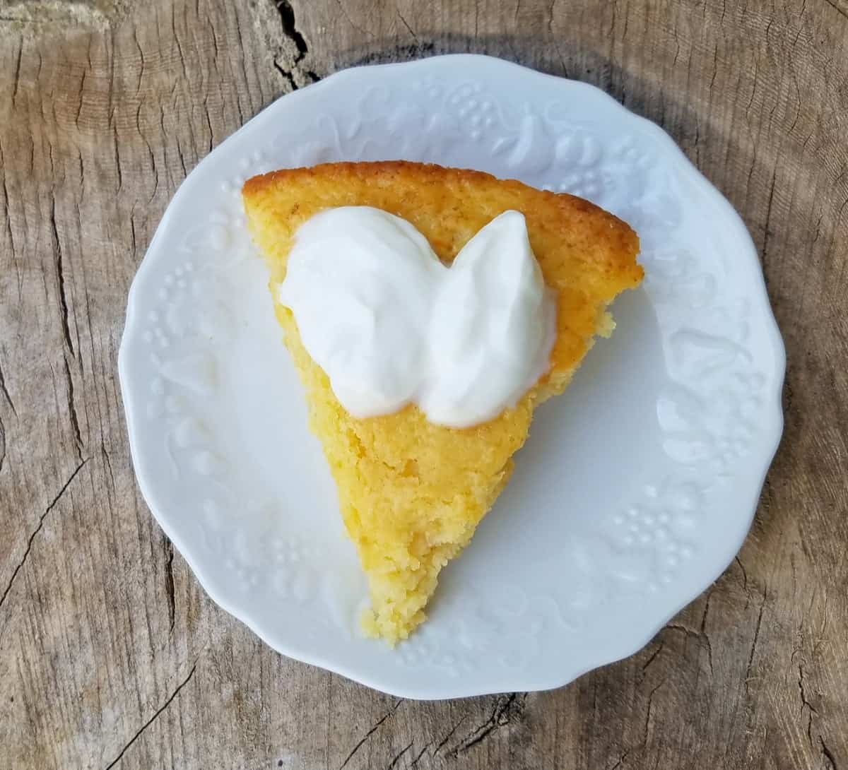 Piece of pineapple apple yogurt cake garnished with whipped cream on white plate.