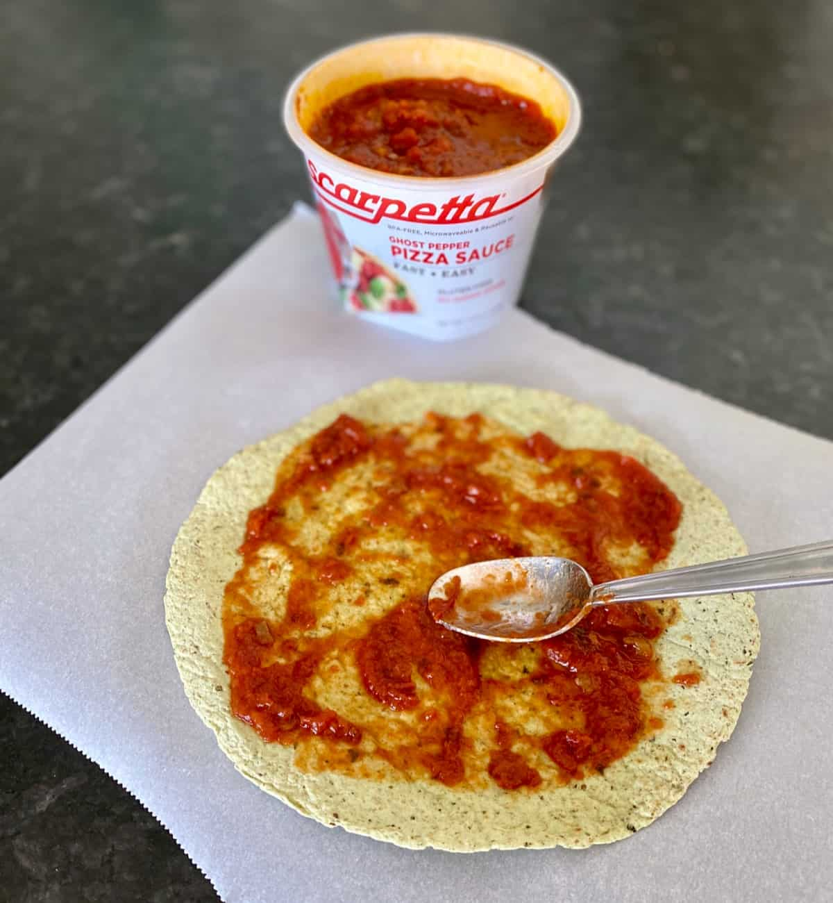Spreading pizza sauce on crispy tortilla with a spoon.