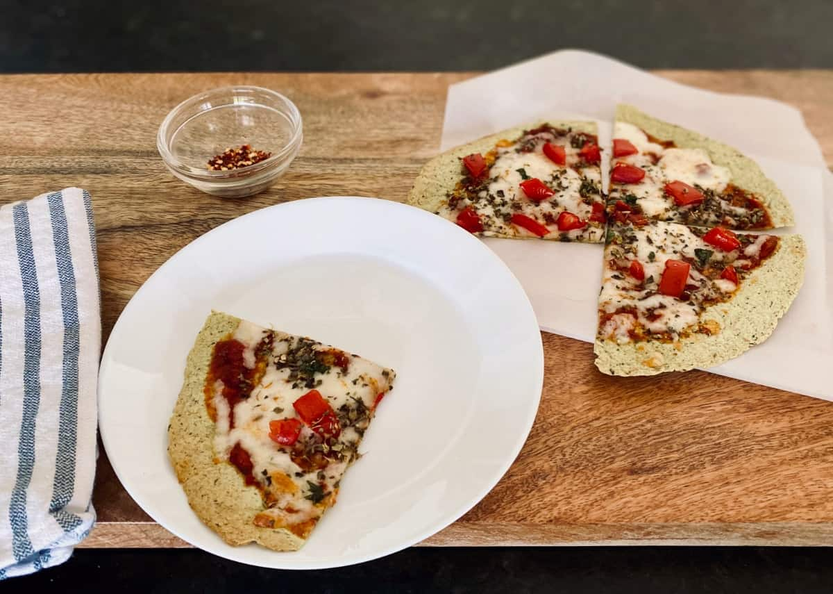 Tortilla pizza cut in 4 slices with one piece on small white plate with red pepper flakes in small glass bowl.