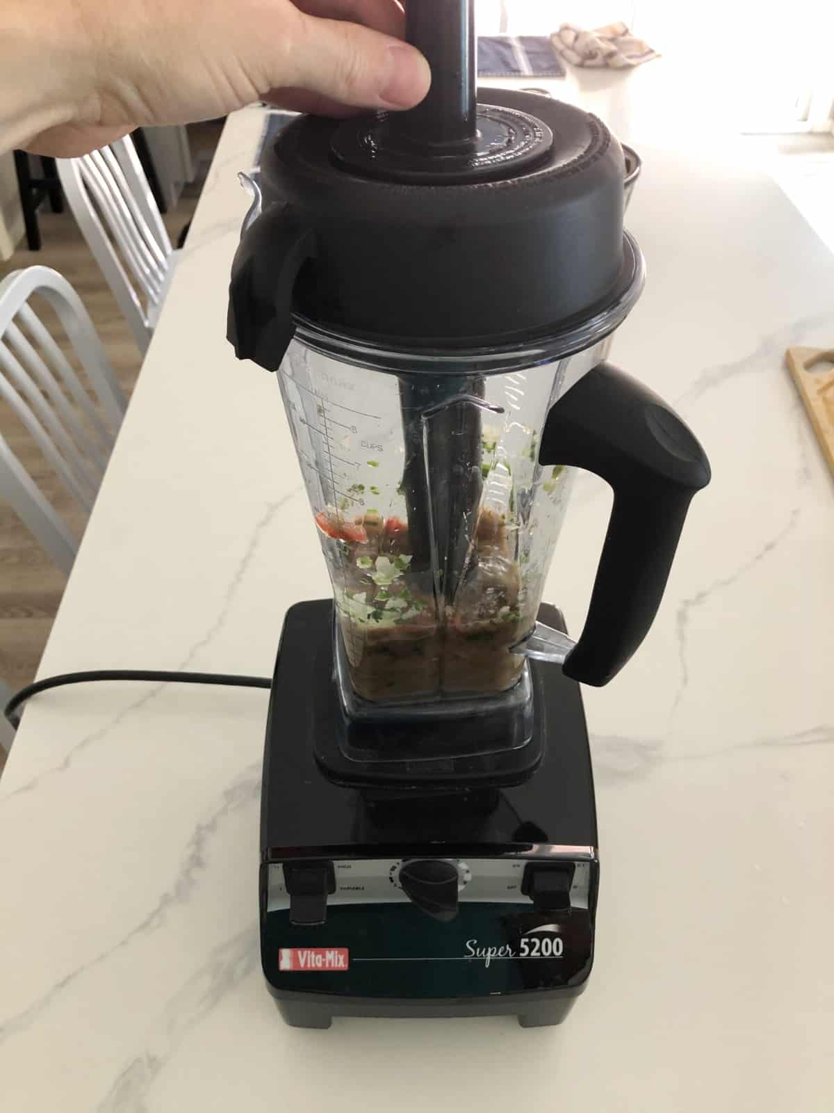 Using tamper with Vitamix blender while making salsa.