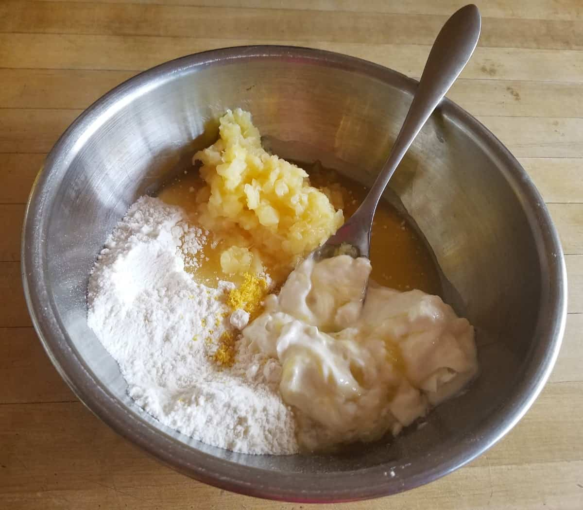 Mixing yellow cake mix, crushed pineapple and yogurt in mixing bowl with a fork.