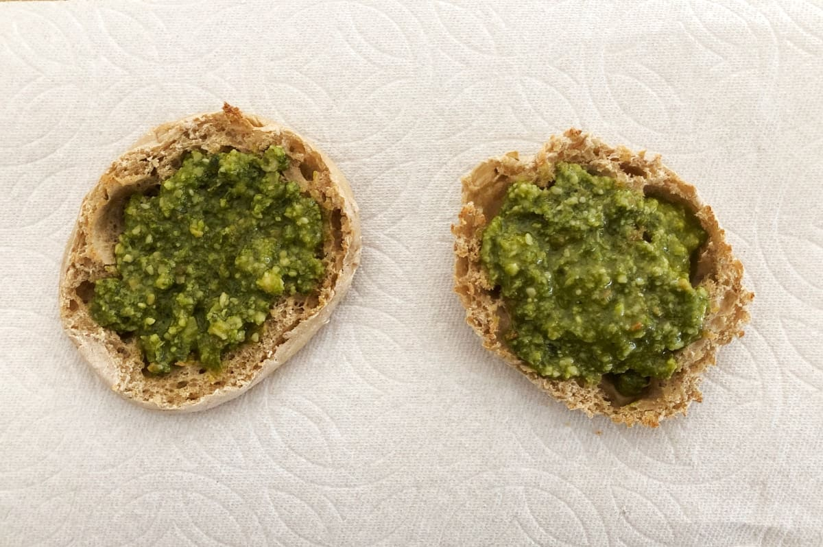 Lightly toasted English muffin topped with basil pesto sauce.