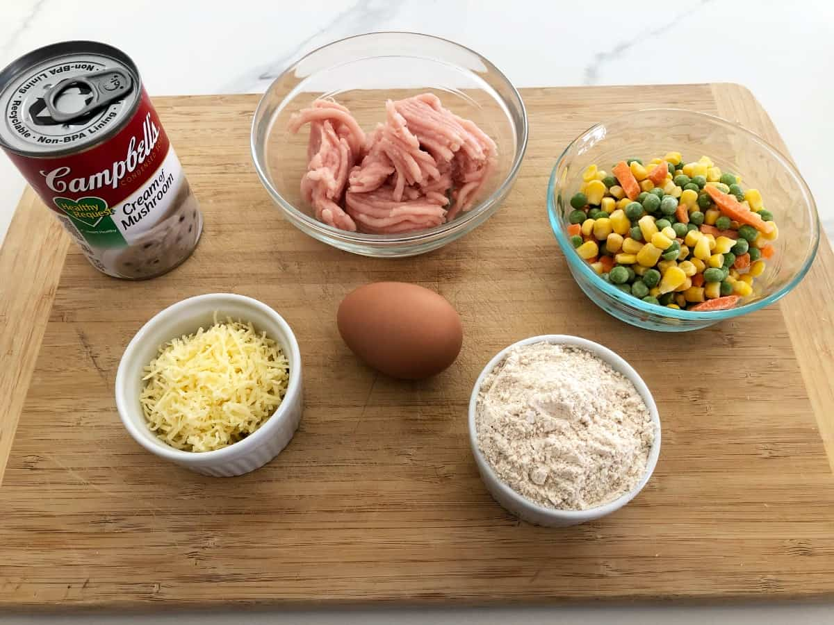 Ingredients on bamboo cutting board, including can of cream of mushroom soup, ground turkey, shredded cheese, egg, baking mix and frozen vegetables.