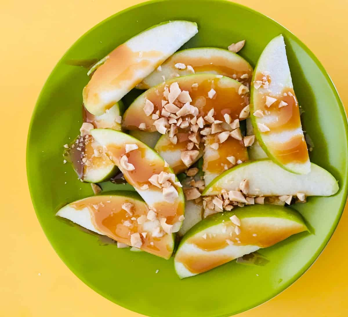 Granny Smith apple slices drizzled with caramel and topped with chopped peanuts on green plate.
