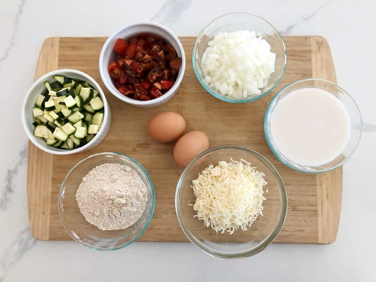 Ingredients for making zucchini pie on bamboo cutting board, including chopped zucchini, tomato, onion, milk, grated cheese, eggs and baking mix.