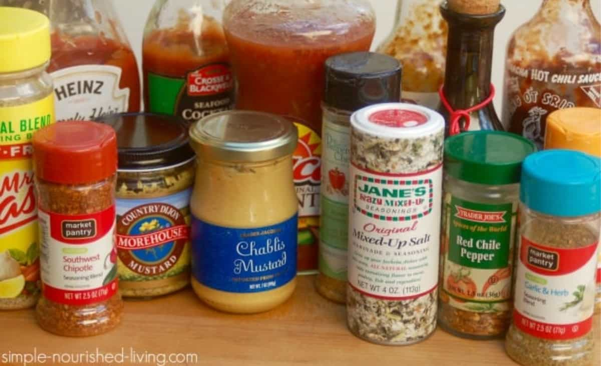 Various bottles of spices including mustards, salsa, salts and crushed red peppers.