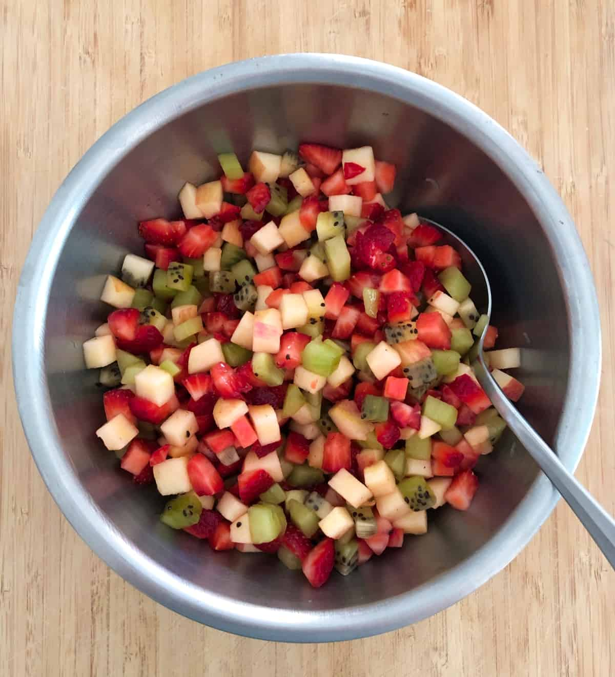 Diced apple, strawberry and kiwifruit in stainless mixing bowl with spoon.