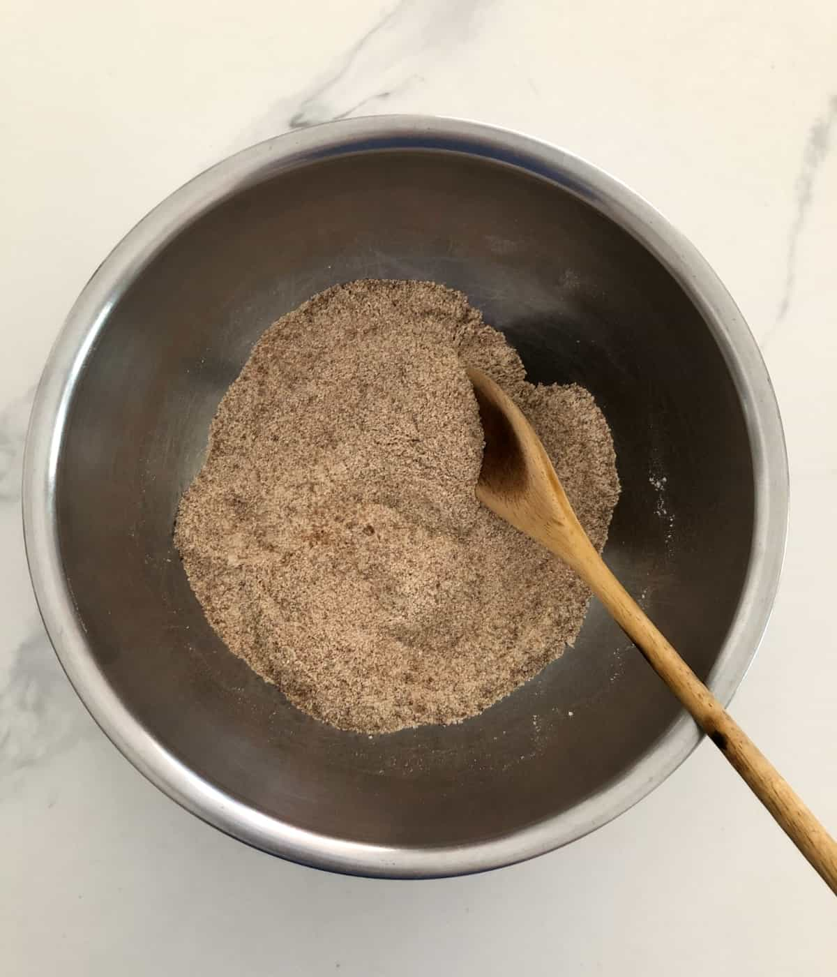 Stirring flour, sugar, salt and cinnamon in mixing bowl with wooden spoon.